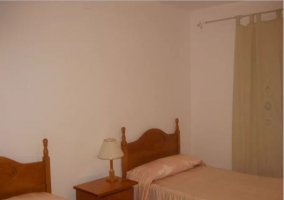 Dormitorio doble con mesilla de madera en el centro