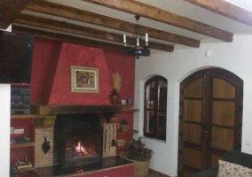 Sala de estar con la chimenea en el frente con vigas de madera