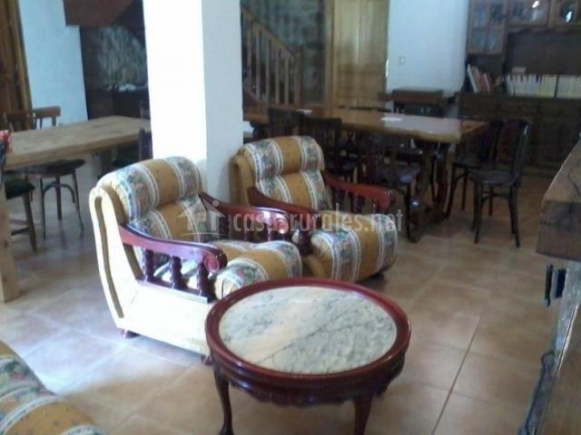Sala de estar y comedor con sillones frente a la chimenea