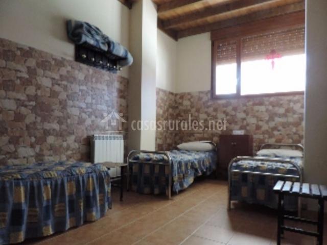 Dormitorio con colchas y techos de madera