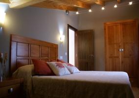 Dormitorio de matrimonio con cabecero de madera y colcha