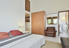 Dormitorio de matrimonio con armario de madera y sillones