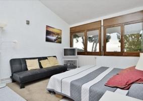 Dormitorio de matrimonio con armario de madera y televisor