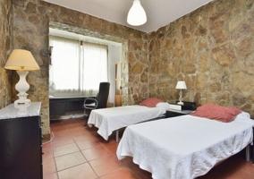 Dormitorio doble con paredes de piedra y ventanas
