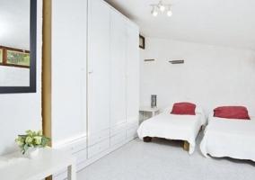 Dormitorio doble en color blanco y cojines en tonos rojos