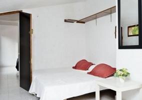 Dormitorio doble en color blanco y cojines rojos