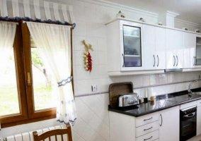 Cocina en blanco y mesa de madera
