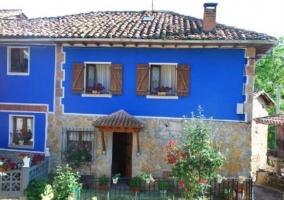 Acceso a la casa con fachada azul y en piedra