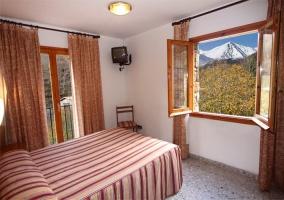 Dormitorio de matrimonio con pared de madera
