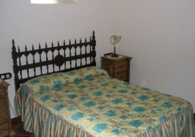 Dormitorio de matrimonio con colchas en azul y amarillo