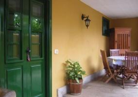 Vistas del porche de la casa con mesa y sillas en madera
