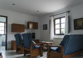 Sala de estar con puerta de madera y sillones tapizados