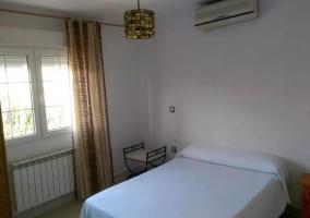 Dormitorio de matrimonio con aire acondicionado y detalles marrones