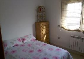 Dormitorio de matrimonio con colcha de flores y mueble con cajones