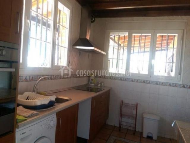 Cocina con muebles de madera y ventanales