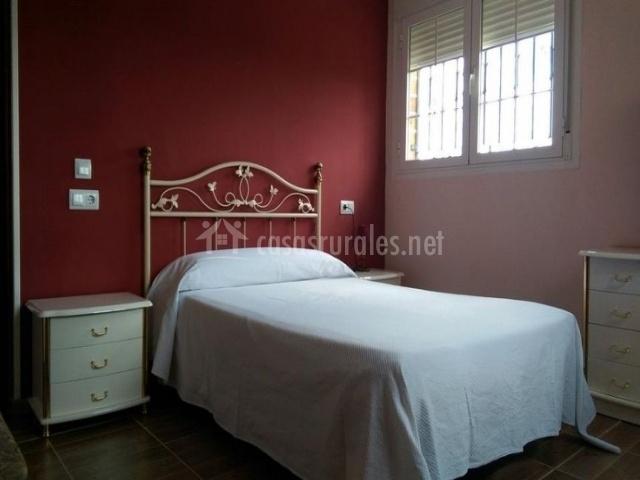 Dormitorio de matrimonio con colcha de color blanco y mesillas de noche