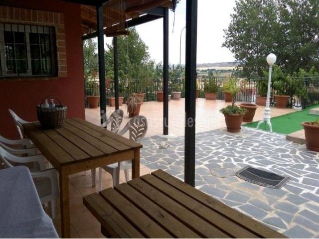 Vistas del porche equipado con mesa de madera y sillas