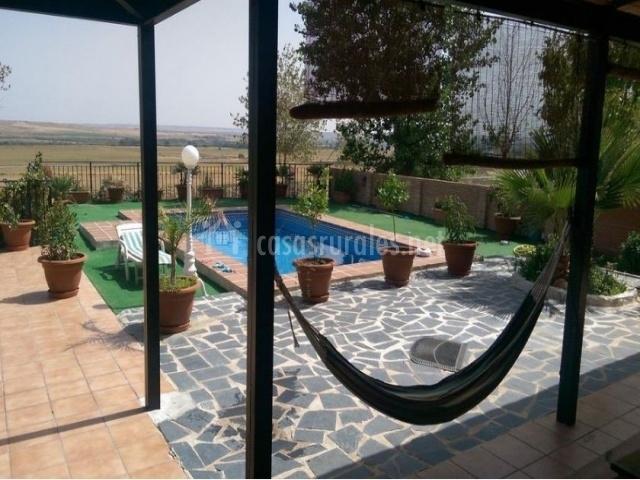 Vistas del porche frente a la piscina con hamaca