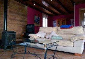 Sala de estar con chimenea y mesa de cristal
