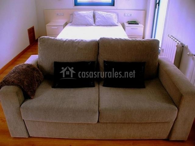 Dormitorio junto al salón con sofá tapizado