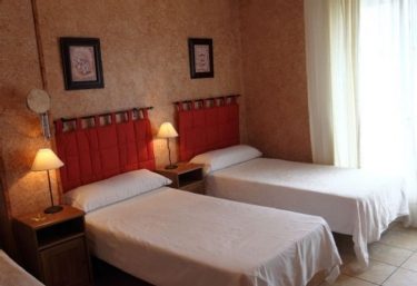 Dormitorio con paredes naranjas y cuadros de flores