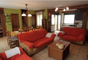 Sala de estar con mantas de color rojo y mesa de madera