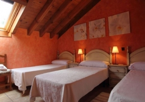 Dormitorio con 3 camas y cuadros