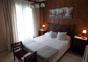 Dormitorio de matrimonio amplio con paredes en madera