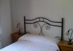 Dormitorio de matrimonio con mesillas de madera y cuadro