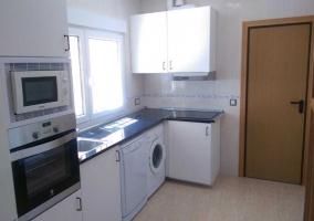 Cocina con armarios en color blanco y microondas