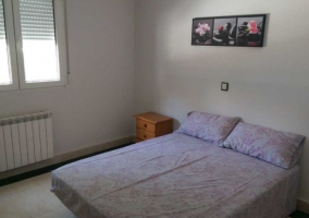 Dormitorio de matrimonio con mesillas de noche y cuadro