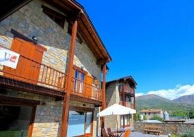 Acceso a la vivienda con fachada en piedra y detalles de madera