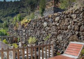 Solárium con tumbonas y muro de piedra
