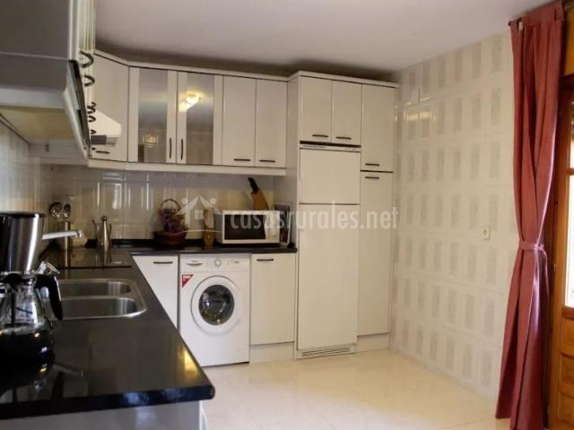 Cocina con armarios en blanco y encimera negra