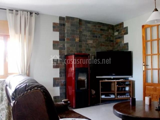 Sala de estar con televisor de plasma junto a la estufa en rojo