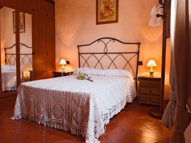 Dormitorio de matrimonio con cabecero de forja negra y manta blanca