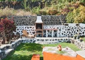 Vistas de los jardines con mesa de madera y la barbacoa