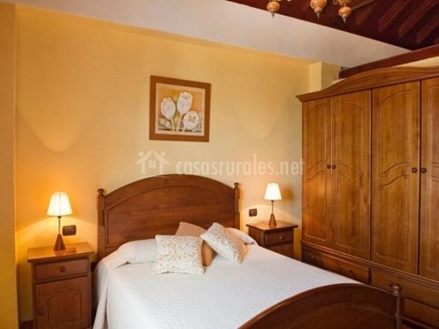 Dormitorio de matrimonio con cuadro en la pared anaranjada