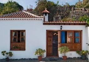 Acceso a la casa con plantas en las ventanas
