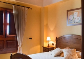 Dormitorio de matrimonio con ventanal y cortina