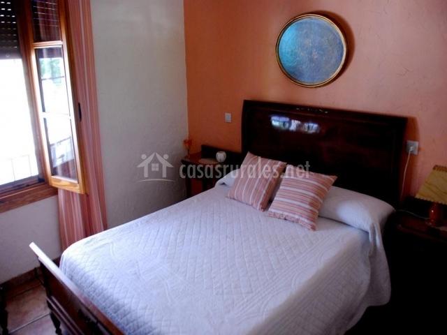 Habitación con cama de matrimonio con muebles de madera y paredes salmón