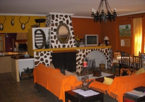 Salón de la casa con sofás marrones y naranjas y suelos de cerámica