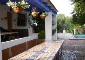 Zona del porche cubierto con mesas y sillas de jardín