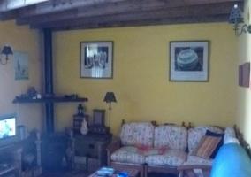 Sala de estar bastante amplia y con la chimenea en una esquina