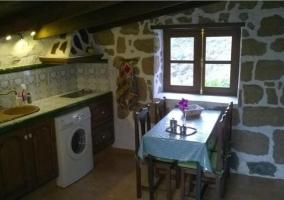 Cocina comedor con lavadora y pared de piedra