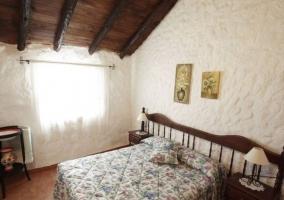 Dormitorio de matrimonio con techos de madera abuhardillados