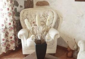 Sala de estar con sillones en blanco y mesa con juego de vajilla