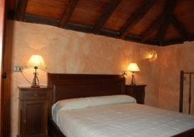 Dormitorio con cama de matrimonio y techos en madera como las mesillas