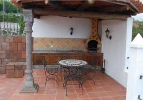 Vistas del porche con la barbacoa y la mesa redonda