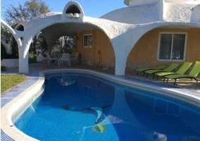 Acceso a la piscina rodeada de zonas verdes